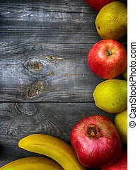 Pomegranate, banana, pear and apple on a gray wooden background
