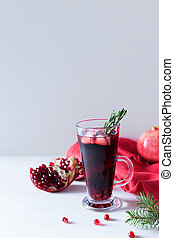 Pomegranate Christmas cocktail with champagne, soda and rosemary on a white table. Xmas drink.