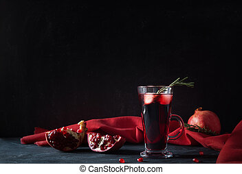 Pomegranate Christmas cocktail with rosemary, champagne, club soda on black table. Xmas drink.