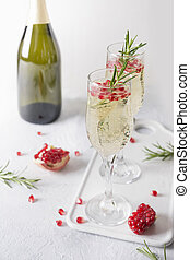Pomegranate Christmas cocktail with rosemary, champagne, club soda on grey table. Xmas Holiday drink.