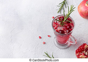 Pomegranate Christmas cocktail with rosemary, cranberry , champagne, club soda on grey concrete table. Xmas drink.