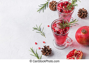 Pomegranate Christmas cocktail with rosemary, cranberry, champagne, club soda on white. Xmas drink.