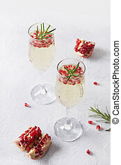 Pomegranate Christmas cocktail with rosemary, sparkling wine on white table. Xmas Holiday drink.