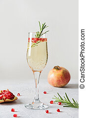 Pomegranate Christmas cocktail with rosemary, sparkling wine on white. Xmas Holiday drink.