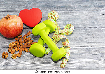 pomegranate fruit, dumbbells, nuts on a wooden background. The concept of health, healthy heart.