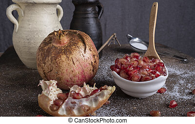 pomegranate fruit with sugar in a cup surrounded by part of the fruit and vases in the background