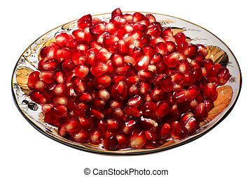 Pomegranate grains on a plate. Isolated on white.