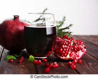 Pomegranate juice and pomegranates on a wooden table