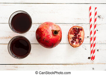 Pomegranate juice on a white wooden