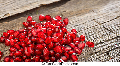 Pomegranate seeds on a wooden table