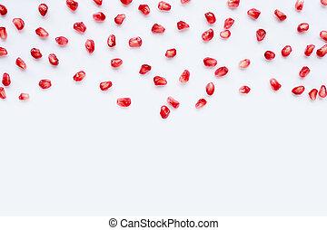 Pomegranate seeds on white background.