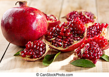 pomegranate with leafs on wooden table