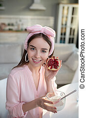 Young pretty girl in a pink headband showing a pomegranate