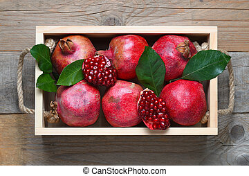 Pomegranates in wooden box top view