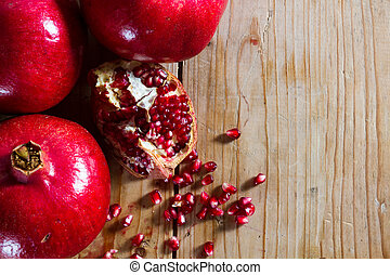 Red, juicy, beautiful organic pomegranate, against a rustic wooden background. Copy space.