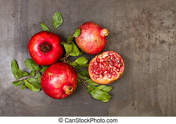 Pomegranates with branches and leaves on a rustic metal table