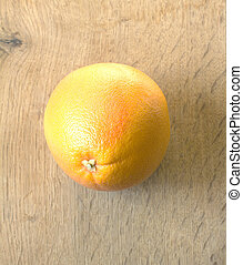 Pomelo on wooden background closeup