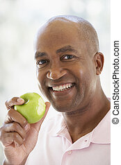 pomme mangeant, milieu, appareil photo, vert, sourire, vieilli, homme