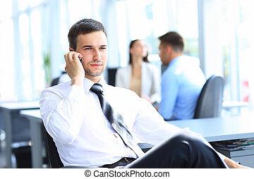 pomyślny, biznesmen, pozować, na, jego, biurko, znowu, mówiąc na ruchomym, w, biuro