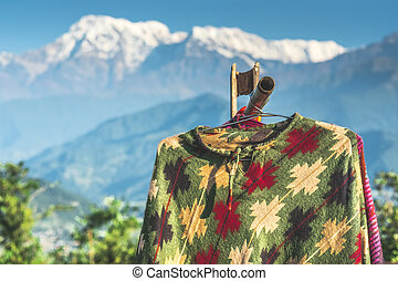Ponchos hanging in front of mountain, Annapurna, Nepal - ...