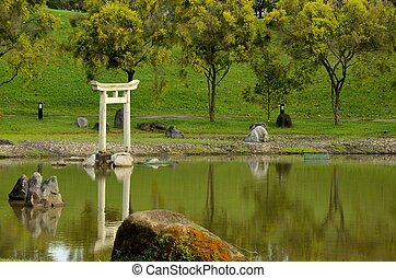 Pond, rocks grass and Japanese arch