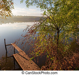Pond shore with old planked footway in autumn morning - ...