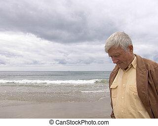 Pondering - Elderly man pondering by the ocean
