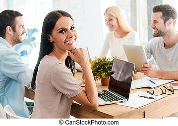 poniendo común, con, colegas., hermoso, mujer joven, llevar a cabo la mano, en, barbilla, y, sonriente, mientras, el sentarse junto, con, ella, colegas, en, el, escritorio, en, oficina