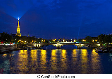 PARIS, FRANCE - AUGUST 6TH 2014: A view at dusk taking in the sights of the Eiffel Tower and Pont des Invalides in Paris on 6th August 2014.