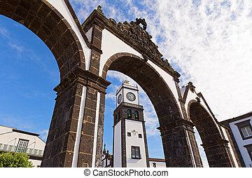 Historic entrance gates (Portas da Cidade) and the clock tower of Saint Sebastian church in Ponta Delgada, Azores, Portugal.