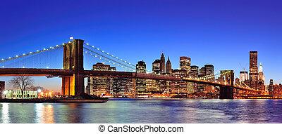 ponte brooklyn, com, cidade nova iorque, manhattan, centro cidade, skyline, panorama, em, anoitecer, iluminado, sobre, rio leste, com, azul, claro, sky.
