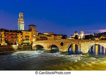 Ancient Roman bridge Ponte Pietra and the River Adige at night illumination, Duomo tower and San Giorgio church in background, Verona, Italy