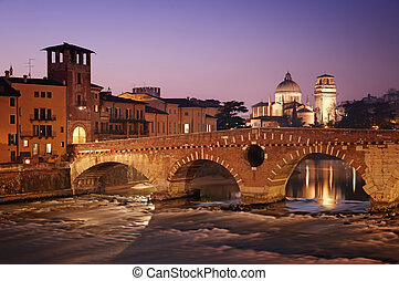 Ponte Pietra and the River Adige at night.