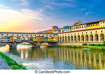 Ponte Vecchio bridge with colourful buildings houses over Arno River reflecting water and embankment promenade archways, historical centre of Florence city, blue evening sky clouds, Tuscany, Italy