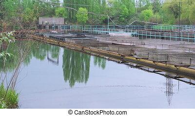 Pontoon sturgeon fish farm on a fresh water river, panning...