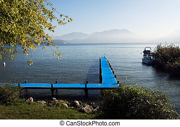 Pontoon with blue carpet and Lake Annecy and its mountain,...
