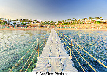 Pontoon with handrails through coral reef to the sea