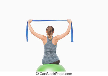 Ponytailed woman training using a resistance band sitting on a fitness ball on white background