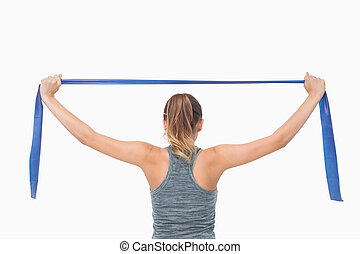 Ponytailed woman training with a resistance band on white...