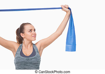 Ponytailed young woman training using a resistance band