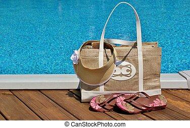 Pool bag - Beach bag with flip flops and a sun visor sitting...
