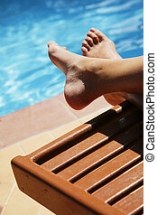 Pool Feet - Feet by swimming pool with sun lounger