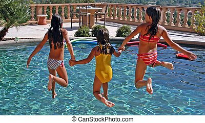 young girls jumping in pool playing together