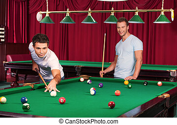 Pool game. Confident young man aiming the billiard ball with cue while his opponent holding billiard cue and smiling on the background