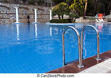 Pool ladder close up. Blue swimming pool