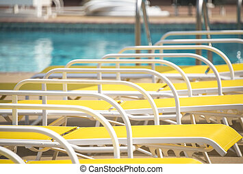 pool lounge chairs - colorful lounge chairs by a pool