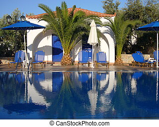 Swimming pool with umbrellas palm tree and reflection