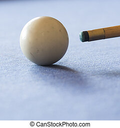 Pool Table - Pool cue and the white ball in shallow focus on...