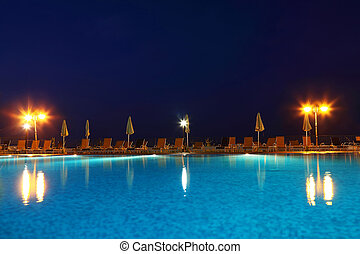 Pool under open-skies in  evening, on  edge of which deck-chairs and umbrellas stand at luminous lanterns