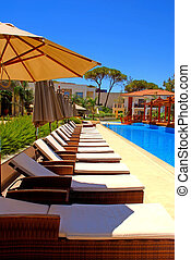 pool with pool bed and umbrella in summer resort